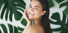 植物に囲まれて美しい肌の女性が笑っている